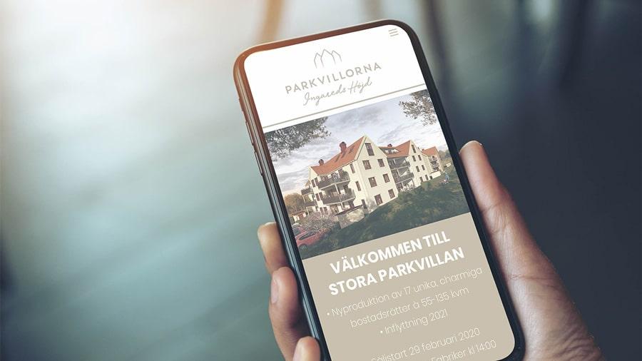 En smartphone som visar Parkvillorna webbplats